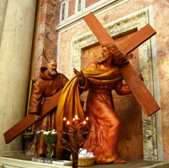 Padre_pio_giving_Jesus_a_hand_with_the_cross.JPG